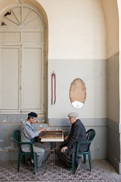 Two men play backgammon in an old tearoom in the city centre.