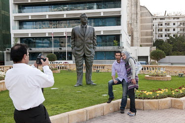 A young Muslim couple are photographed beside the statue of former Prime Minister Rafic Hariri at the spot where he was killed by a car bomb in 2005.