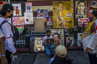 A woman gets her picture taken in front of a painting of Aung San Suu Kyi at 'Artists' Street', a pop-up stall creating and selling artworks in order to fund the Civil Disobedience Movements protestin...