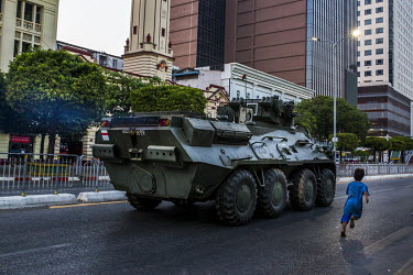 A child runs as an armoured military vehicle drives along Sule Pagoda road in the city centre.