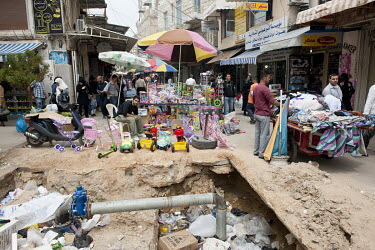 Market stalls beside a hole in the street excavated to access water pipes.