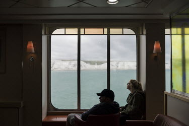 A couple look out of a window towards the White Cliffs of Dover as they sail in a ferry from Calais to Dover.
