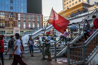A man carries a National League for Democracy (NLD) flag in Sule square where large crowds gathered show their support for democracy, Aung San Suu Kyi and the NLD, and to protest the 1 February 2021 m...