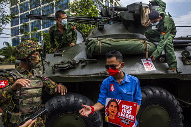 A protestor stands beside an armoured military vehicle, near the Central Bank as nearby tens of thousands of people gathered in front of the Central Bank to protest against the military dictatorship a...