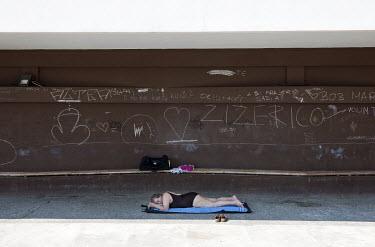 A woman sleeps beside a graffiti-covered wall on the Adriatic coast.