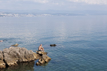 A man sits on a rock looking over the Adriatic Sea, with the city of Rijeka in the background.