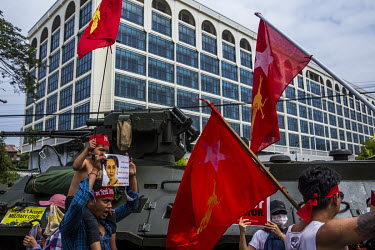 People gather beside an armoured military vehicle near the Central Bank to protest against the military dictatorship and to show support for the Civil Disobedience Movements.