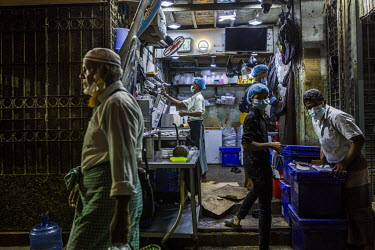 Staff working in a small shop selling ice cream shortly before the military's 8pm-4am curfew begins.
