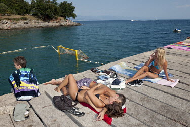 Young couple lie in each others arms on a jetty on the Adriatic coast.