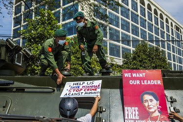 Soldiers come out of their armoured vehicle to remove protest placards that were placed by protestors as tens of thousands of people gathered in front of the Central Bank to demonstrate their support...