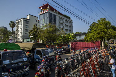 Riot police stand behind a barrier as they block a road preventing protestors to gather outside the National League for Democracy (NLD) headquarters.