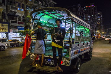 A private transport vehicle, displaying a National League for Democracy (NLD), flag waits for passengers shortly before the military's 8pm-4am curfew begins.