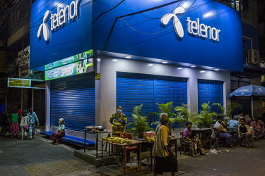 A woman selling bananas from a stall outside a closed telecoms outlet store shortly before the military's 8pm-4am curfew begins.