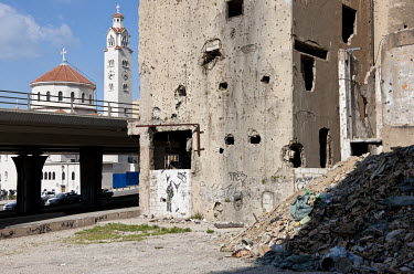 A derelict building on the former demarcation line pock-marked with shrapnel damage from the civil war. In the background is the Armenian Catholic Cathedral of Saint Elias and Saint Gregory the Illumi...