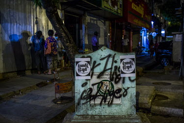 A pillar displaying the USDP party logo covered with graffiti and posters in support the anti-coup Civil Disobedience Movements.