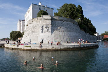 People swim in the sea beside a Venetian-era city wall decorated with a lion bas relief.