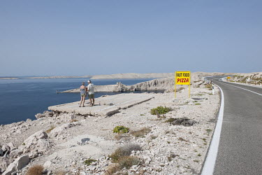 A couple look over the coast towards the barren island of Pag.