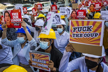 Students from the University of Economics hold up signs featuring the image of Aung San Suu Kyi as they march in support of the National League for Democracy (NLD) and democracy, and to protest the 1...