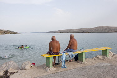 Two men sit on a bench watching children play in the water on the isle of Pag.