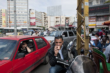 A man drinks coffee at a busy road junction in the Dora neighbourhood.