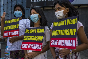 Women and children stand in front of a shopping centre holding placards demonstrating in support of democracy, Aung San Suu Kyi and the National League for Democracy (NLD) and to protest the 1 Februar...