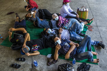 Protestors check their mobile phones as they rest beneath a fly-over after they spent the morning demonstrating in support of democracy, Aung San Suu Kyi and the National League for Democracy (NLD) an...
