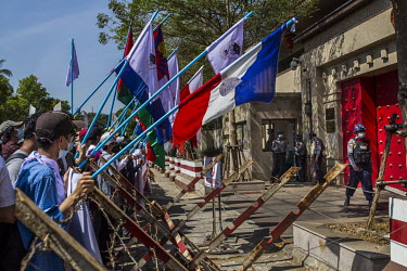 Protestors carrying flags representing some of Burma's ethnic minorities gather behind police barriers at the Chinese embassy where anti-coup protestors have gathered to voice their disapproval of the...