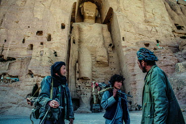 Hazara fighters, from the Hesbe-Wahdat-e Islami political group, stand below the 'Western' Bamiyan Buddha (6th-7th century CE), one of two giant rock-carved Buddha statues , prior to their destruction...