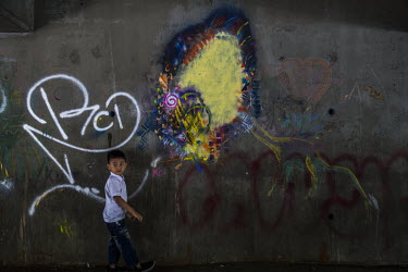 A child stands beside a wall where a graffiti art portrait of Aung San Suu Kyi has been painted over.