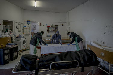 Funeral Director Kafil Ahmend (middle), helped by two mortuary workers, prepares the shroud for a COVID-19 victim at the Al Birr Islamic Trust mortuary in south London.