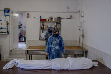 Nasim Ahmed stands beside the shrouded body of a COVID-19 victim in the mortuary of the Al Birr Islamic Trust in south London.
