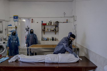 Funeral director Kafil Ahmed performs a 'dry ablution' on the shrouded body of a COVID-19 victim in the mortuary of the Al Birr Islamic Trust in south London.Funeral director Kafil Ahmed performs a 'd...