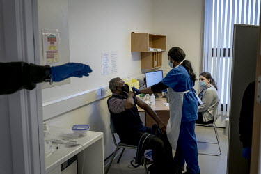A doctor administers the Astra Zenica vaccine at the Waldron Health Centre in south London.