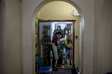 A woman is helped into the Bloomsbury Surgery building where she has come to get her COVID-19 vaccination.A woman is helped into the Bloomsbury Surgery building where she has come to get her COVID-19...