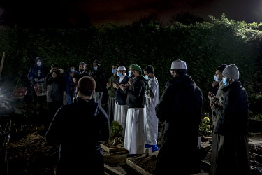 Mourners say prayers at the grave of a man who died of COVID-19 during his funeral at the Muslim Patel Burial Trust cemetery in east London which is run by Supporting Humanity, a bereavement charity.M...