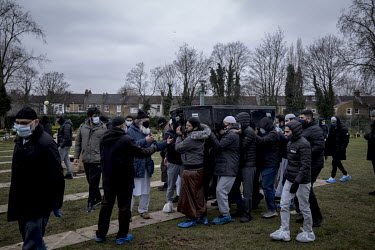 The coffin containing the body of a man who died of COVID-19 is carried to the graveside for burial at the Muslim Patel Burial Trust cemetery in east London which is run by Supporting Humanity, a bere...