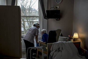 A care worker at St Cecilia's nursing home tends to a 97 year old COVID-19 positive patient recently transferred from hospital to the home's COVID-19 secure floor. During the first wave residents died...