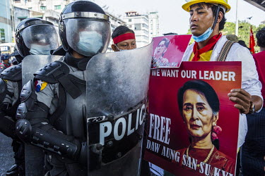 An anti-coup protestor holding a poster of Aung San Suu Kyi stands beside riot police during protests against the 1 February 2021 military coup and in support of the Civil Disobedience Movement.