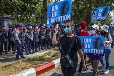 Anti-coup activists carrying placards with the slogan 'Join our revolution' over the image of President Jo Biden during protests against the 1 February 2021 military coup and in support of the Civil D...
