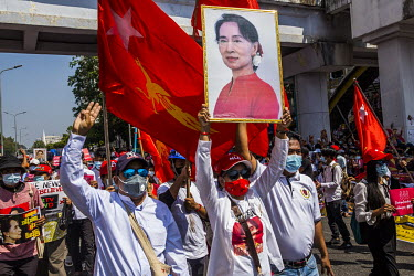 Party members from the National League for Democracy (NLD) march with NLD flags and pictures of Aung San Suu Kyi as a huge crowd gathered in the city centre around Sule Square to protest the 1 Februar...