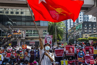A man waves a National League for Democracy (NLD) flag and people hold up pictures of Aung San Suu Kyi as a huge crowd gathered in the city centre around Sule Square to protest the 1 February 2021 mil...