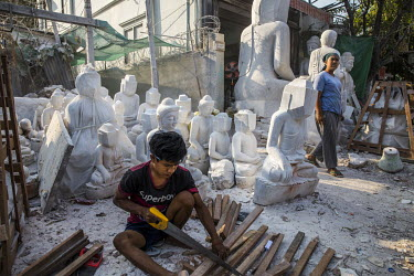 A woman looks at the activity of nearby security forces while a stone-carver continues their work.