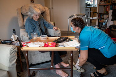 A care assistant helps a 90 year-old woman get ready to visit a vaccination centre for her second Pfizer-BioNTech vaccination to protect her against COVID-19.