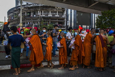 A group of Buddhist monks donate snacks and water to protestors at Myaynigone junction.