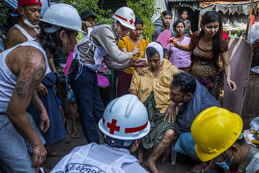 Family and neighbours gather round as volunteer medics treat U Thein Htay who was beaten up by a group of pro-military supporters including monks that came into their neighbourhood armed with swords a...