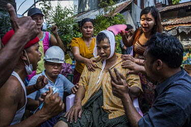 Family and neighbours help U Thein Htay who was beaten up by a group of pro-military supporters including monks that came into their neighbourhood armed with swords and sticks and attacked local resid...