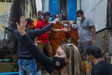 A man tries to keep the peace as an argument grows between a group of Buddhist monks, from a monastery said to be known for its nationalist, pro-military supporting monks, and pro-democracy protestors...
