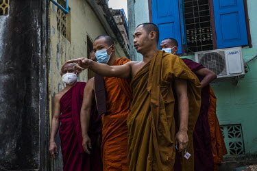 Buddhist monks, from a monastery said to be known for its nationalist, pro-military supporting monks, talk to pro-democracy protestors at the gates of their compound after it was claimed a group of pe...