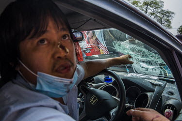 U Than Win (50), whose face is bloodied, points to his broken car windscreen. Win says he was beaten by a group of pro-military people and monks armed with wooden sticks and iron rods while he was par...