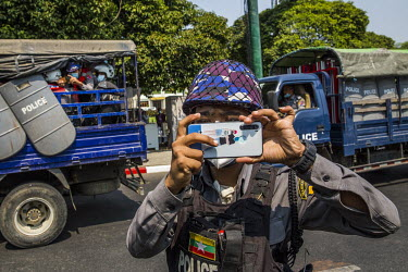 A police officer photographs journalists and protestors.
